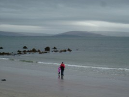 Father and daughter standing together on the shore, Co. Galway